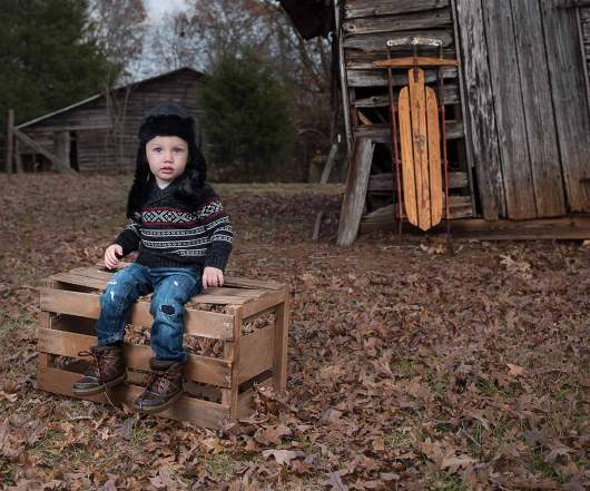 Boy Sitting on Crate in Christmas Sweater