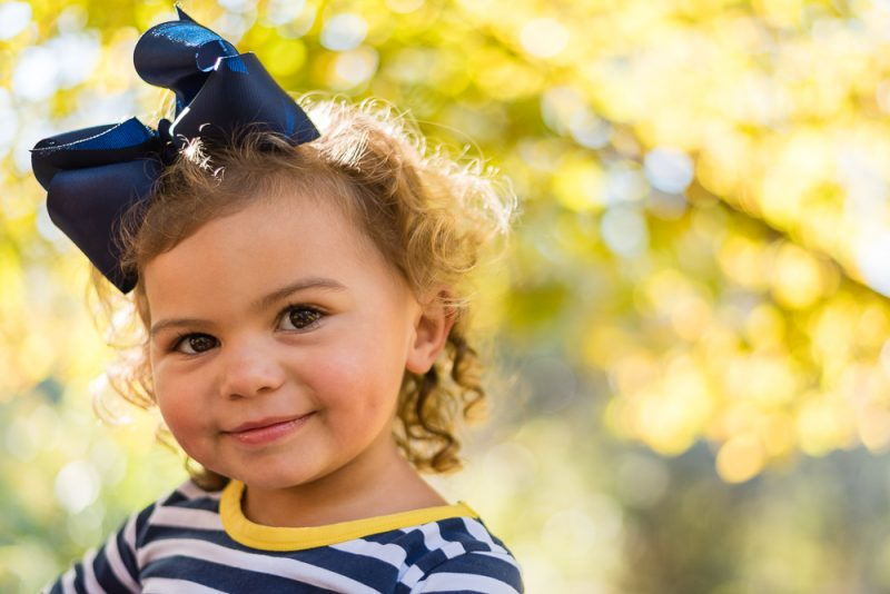 Little Girl in Striped Outfit During Fall