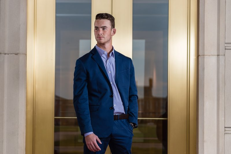 High School Senior in Suit in front of Gold Doors
