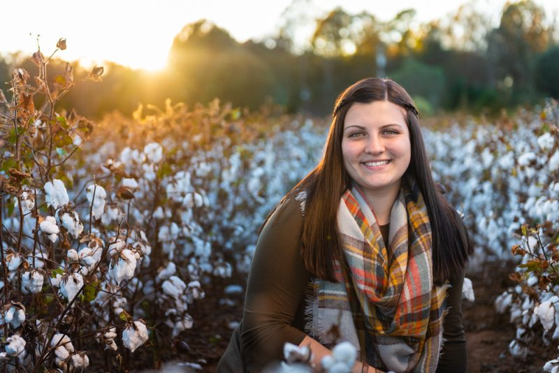 HS Senior sitting in cotton field at sunset