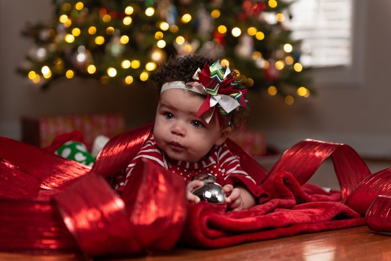 Little girl laying in christmas ribbon